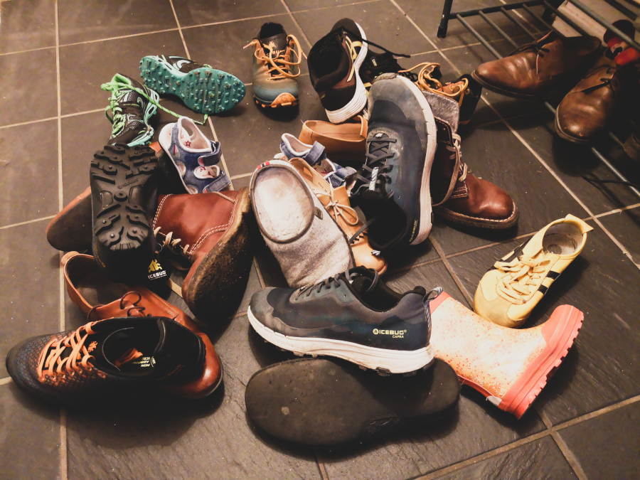 Masse sko som ligger hulter til bulter på golvet. Foto.